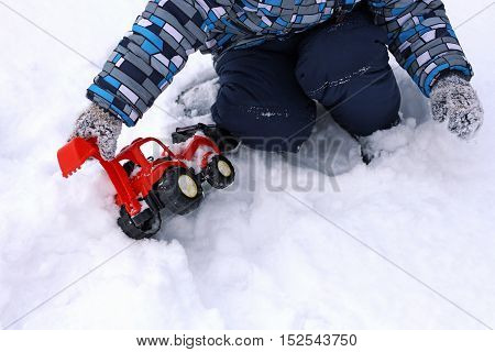 Part of the image of a small child who sits in the snow and plays with a red toy excavator car.