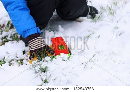 Part of the image of a small child who is sitting in the first snow and plays with a red toy car.