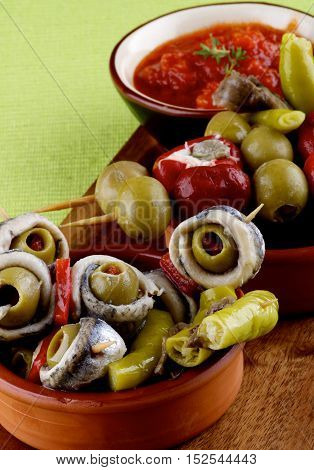 Delicious Spanish Snacks with Anchovies Green Olives Small Peppers Stuffed with Cheese and Tomatoes Sauce in Various Bowls closeup on Green Napkin. Focus on Foreground