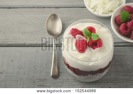 Healthy breakfast, desert, with chia seed pudding, cream, raspberry jam, coconut flakes and fresh berries, on wooden background, toned
