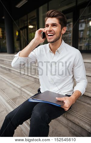 Happy young businessman holding folder with documents and talking on cell phone outdoors