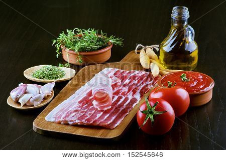 Pancetta on Wooden Cutting Board and Ingredients with Tomatoes Garlic Rosemary Tomato Sauce Bread Sticks Spices and Olive Oil closeup on Dark Wooden background