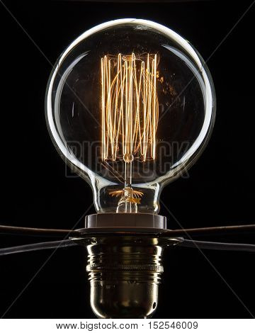 Electric Lamp round on a black background with a burning coil