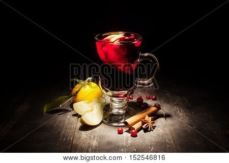 mulled wine with apple and mandarin on a black background