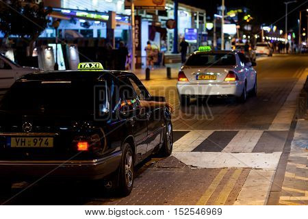 CYPRUS, PROTARAS - 10 OCT 2016: Taxi cars driving at night street in Protaras