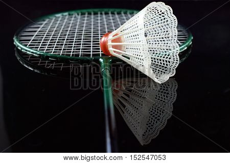 Badminton racket and shuttlecock closeup isolated on black mirroring background.