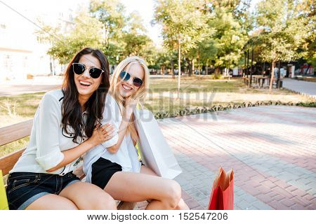 Two beautiful young girls in sunglasses resting on bench after shopping