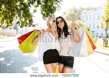Two girls walking with shopping bags on city streets together