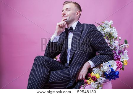 Elegant groom looking away while sitting on chair against pink background