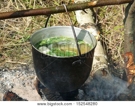 fish soup a bowler hat over a campfire after a successful fishing.