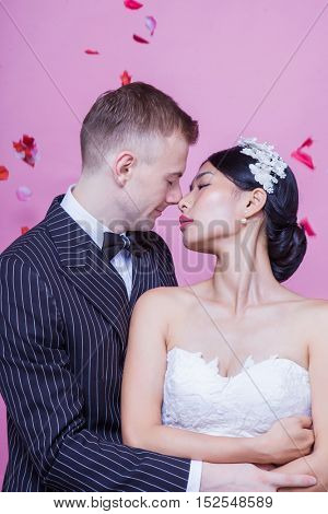 Side view of romantic wedding couple embracing against pink background