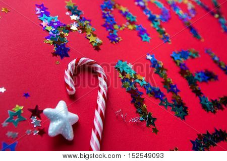 inscription colored stars new year on a red background with a large festive candy