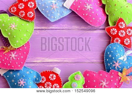 Different Christmas ornaments. Felt Christmas trees, mittens, hearts, stars on lilac wooden background with blank space for text. Winter festive background. Top view