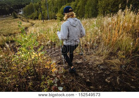 young woman with walking sticks down mountain on track of dirt and stones