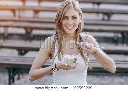 beautiful girl eats salad in the Park