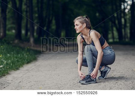 athletic girl running in the Park and doing exercises Jogging