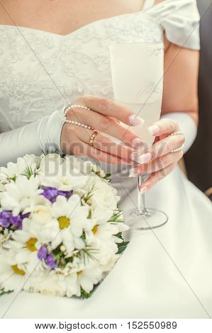 Bride holding decorated champagne crystal glass and bouquet