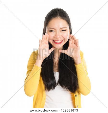 Portrait of Asian woman, shouting and looking at camera, standing isolated on white background.