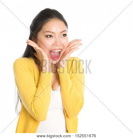 Shocked Asian woman mouth open wide, shouting and looking at side, standing isolated on white background.