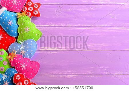 Colorful Christmas ornaments. Felt Christmas trees, mittens, hearts, stars on lilac wooden background with empty space for text. Merry Christmas and Happy new year background. Top view
