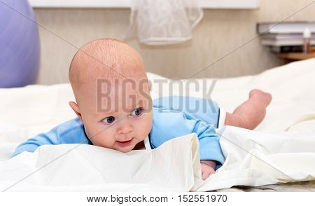 Indoor close up shot of boy lying on stomach