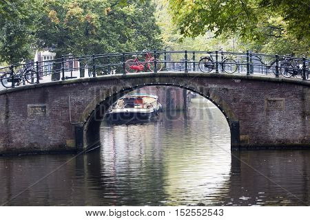Canal and a red bike parked on a bridge in Amsterdam