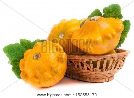 yellow pattypan squash with leaf in a wicker basket isolated on white background.