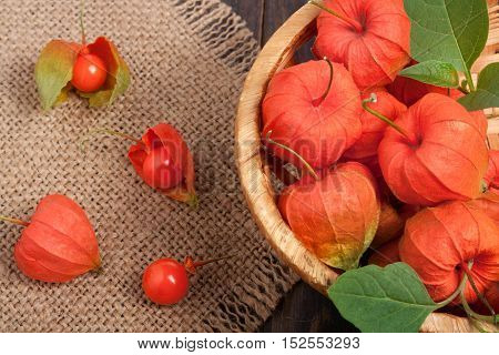 physalis in a wicker basket on the table with a napkin of burlap