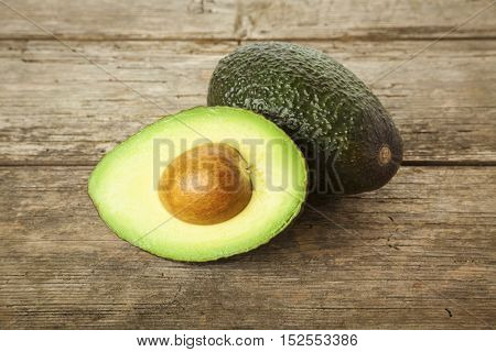 Whole and halved avocado fruit on rustic wooden background