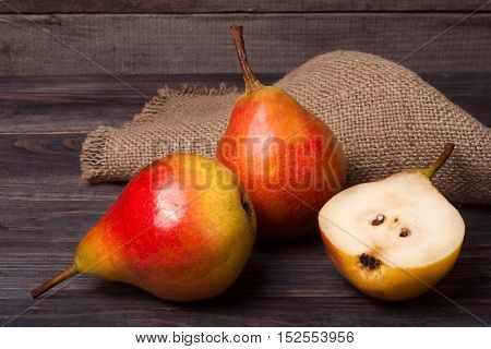 two pears with half on a dark wooden background.