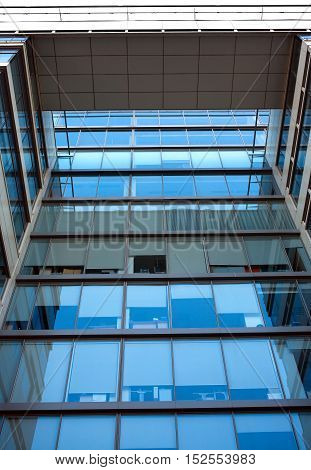 Facade with glass wall of modern office building with many large panoramic windows with gray curtains in business cluster front view close-up