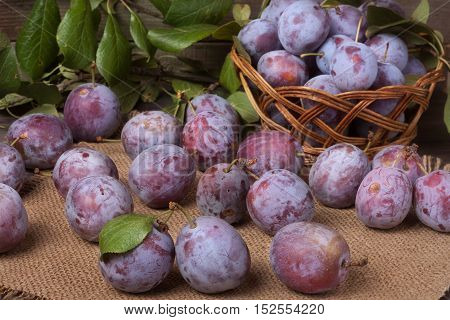 plums in a wicker basket on the wooden background with sackcloth.
