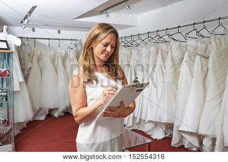 Female Bridal Store Owner With Wedding Dresses