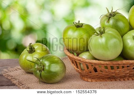unripe green tomatoes in a wicker basket on a wooden table with a blurred background.