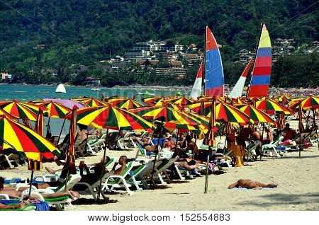 Phuket Thailand - January 11 2011: A sea of colourful umbrellas and white deck chairs dot the soft sands of Patong Beach