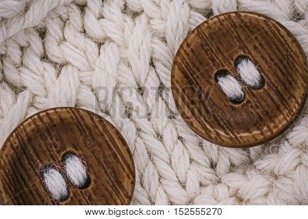 Macro flat view of knitted undyed wool surface with buttons