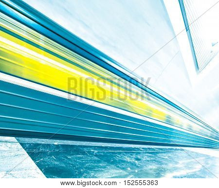 Perspective and diminishing wide angle view of modern light blue illuminated and spacious public metro marble abstract station, fast blurred trail of quick urban train in vanishing traffic motion way