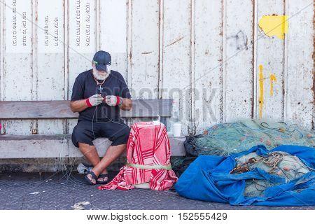 Elderly Fisherman Sits On The Waterfront And Repairing Fishing Net