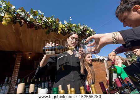 TBILISI, GEORGIA - OCT 16, 2016: Woman in national Georgian costume pours wine into a glass during festival Tbilisoba on October 16, 2016. Tbilisoba is traditional festival in capital of Georgia from 1979