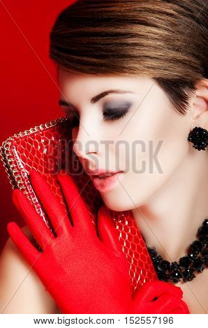 Beautiful girl with a red purse. Makeup. Accessories. Model with red lipstick