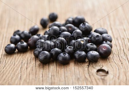 closeup of a pile of ripe blueberries on a rustic wooden table