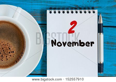 November 2nd. Day 2 of month, calendar and cup with hot coffee at teacher workplace background. Autumn time, top view.