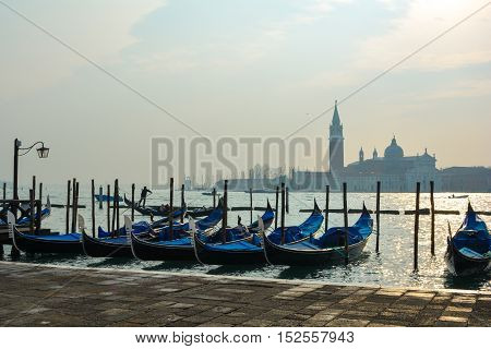Typical Italian gondola boats with bell tower in backgroud. Romantic view before sunset.