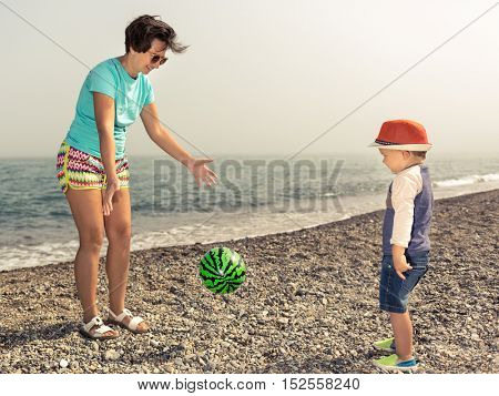Mother and son playing ball near the sea