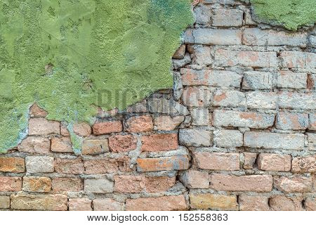 green plaster has cracked to reveal a worn brick wall below street wall background texture .
