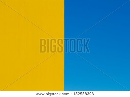 An architectural abstract, half and half  image showing the edge of a bright yellow wall bisecting the frame with a clear blue sky on the other side.
