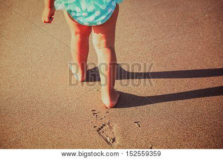 family beach vacation - little girl feet walk on beach