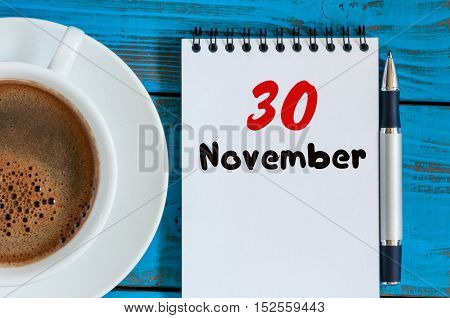 November 30th. Day 30 of month, calendar on hot coffee cup at translator or interpreter workplace background. Autumn time.