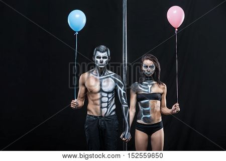 Gorgeous couple of pole dancers holds their hands together next to a pylon on a dark background in the studio. They have body-art and wears black clothes. Girl and guy hold blue and pink balloons.