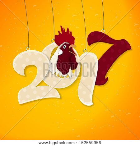 Creative hanging text 2017 with rooster on yellow background for Chinese New Year or Year of the Rooster celebration.